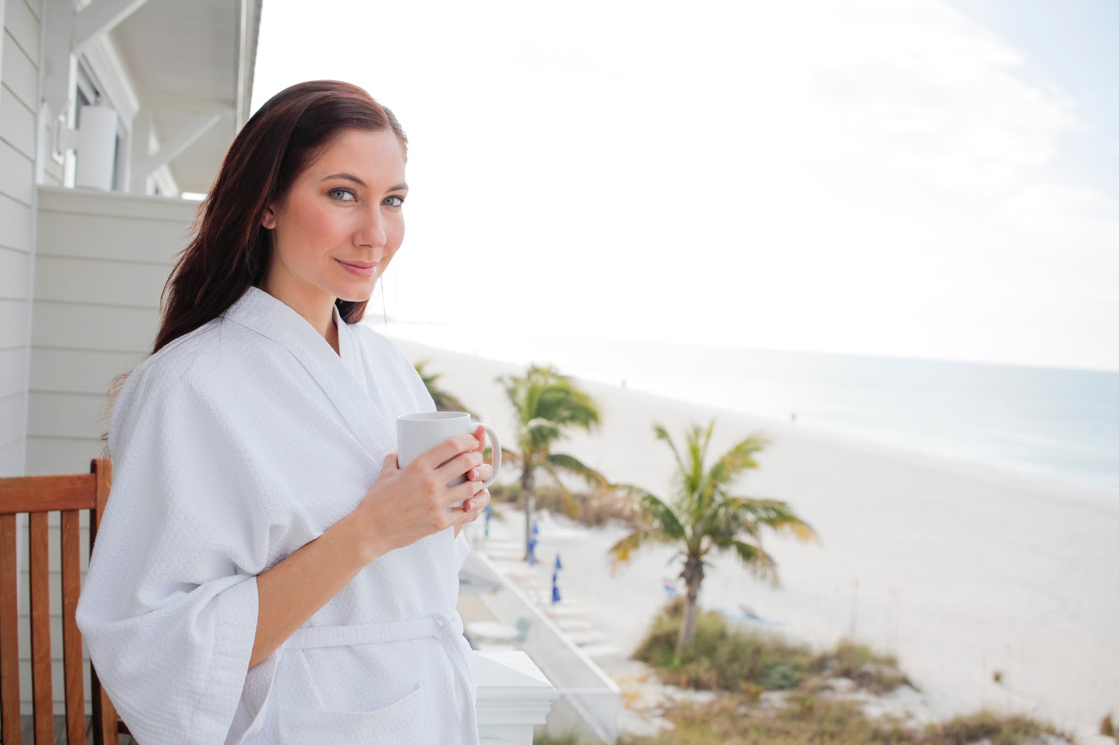 Amy West enjoying coffee on the patio of Mainsail Beach Inn overlooking the beach and Gulf.