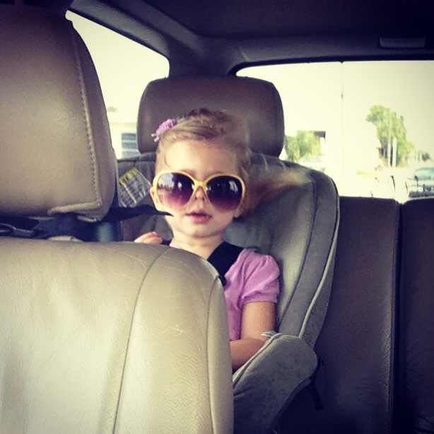 Cute toddler in carseat with sunglasses