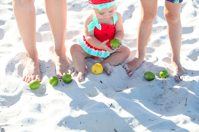 infant in watermelon bathing suit playing with limes