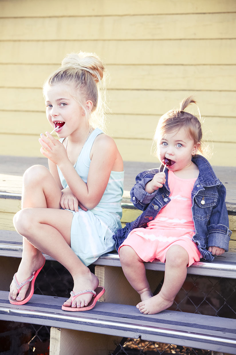 Sisters sit on the steps and enjoy lollipops in Sunuva